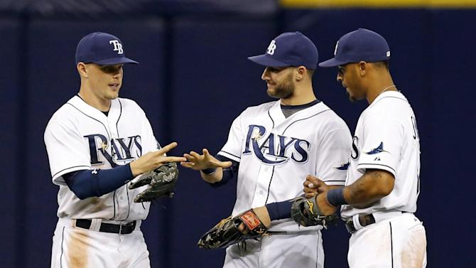 Tampa Bay Rays outfielders, from left, Brandon Guyer, Kevin Kiermaier and Desmond Jennings play rock, paper, scissors after the final out of a baseball game against the Toronto Blue Jays on Friday, April 24, 2015, in St. Petersburg, Fla. The Rays won 12-3. (AP Photo/Mike Carlson)