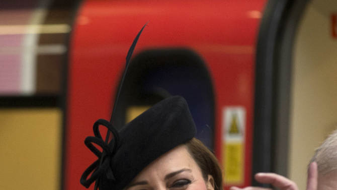 """Britain's Kate, the Duchess of Cambridge, reacts as she is presented a badge that says """"Baby on Board"""", normally available to pregnant passengers to encourage others to give them a seat, watched by Britain's Queen Elizabeth II, bottom, at Baker Street underground station in London, for a visit to mark the 150th anniversary of the London Underground, Wednesday, March 20, 2013.  The Queen made her first public engagement in more than a week Wednesday after cancellations following her hospitalization for a stomach bug.  The British head of state joined her husband Prince Philip and their granddaughter-in-law, Kate, for the event marking the 150th anniversary of London's sprawling subway system, affectionately known as the Tube.  (AP Photo/Matt Dunham)"""
