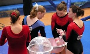 Gymnasts pepare their hands with chalk.