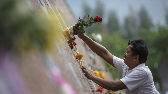A man climbs to put flowers on a wave-shaped tsunami monument for victims of the 2004 tsunami in Ban Nam Khem