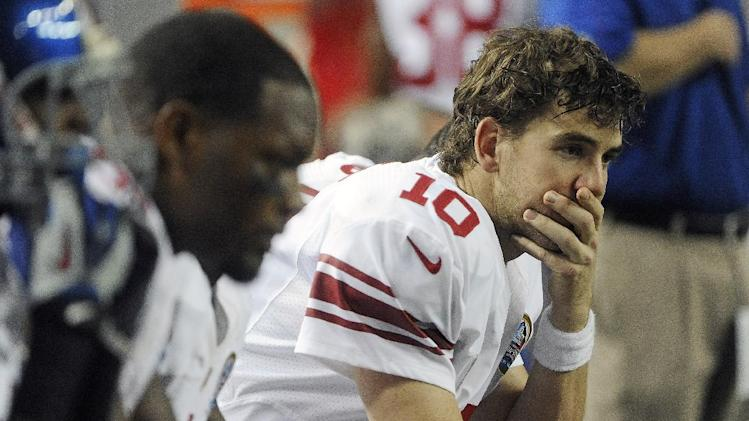 New York Giants quarterback Eli Manning (10) sits on the bench during the second half of an NFL football game against the Atlanta Falcons, Sunday, Dec. 16, 2012, in Atlanta. (AP Photo/John Amis)