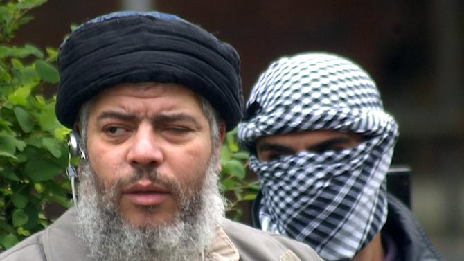 FILE - This Friday, April 30, 2004 file photo shows Muslim cleric Abu Hamza al-Masri, as he arrives with a masked bodyguard, right, to conduct Friday prayers in the street outside the closed Finsbury Park Mosque in London. Britain is set to extradite its most recognizable extremist, Abu Hamza al-Masri, to the United States, sending a national hate figure to face charges of helping set up a terrorist training camp in rural Oregon. Britain's Home Office said Monday Sept. 24, 2012 that radical Muslim cleric Abu Hamza al-Masri has lost an appeal regarding his extradition to the United States. (AP Photo/Max Nash, File )