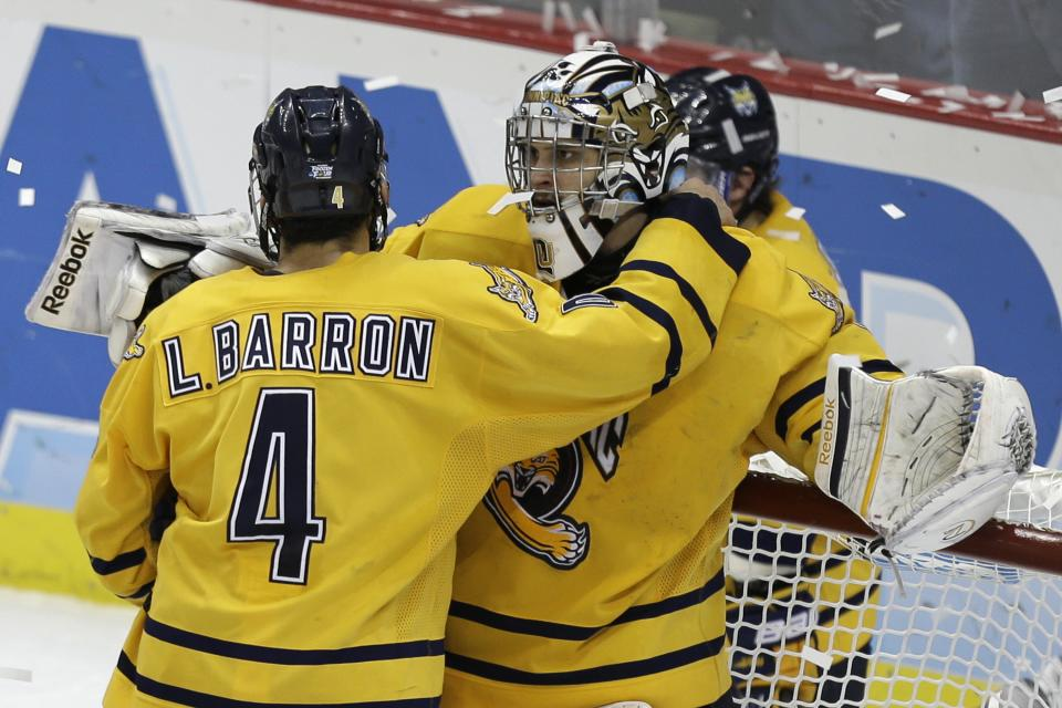 The Quinnipiac goalie Eric Hartzell, right, is comforted by Loren Barron (4) after losing to Yale 4-0 in the NCAA men's college hockey national championship game in Pittsburgh Saturday, April 13, 2013. (AP Photo/Gene Puskar)