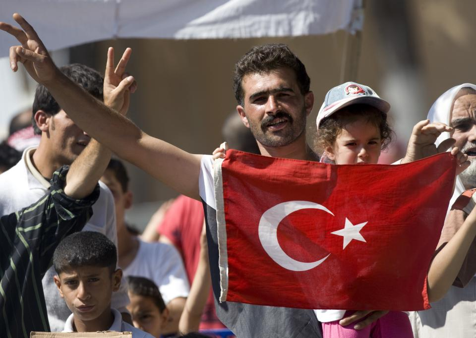 A man holds a Turkish national flag as Syrian refugees demonstrate against their country's regime and its leader Bashar al-Assad, in a camp in the Turkish border town of Yayladagi in Hatay province, Turkey, Wednesday, June 29, 2011.(AP Photo/Burhan Ozbilici)