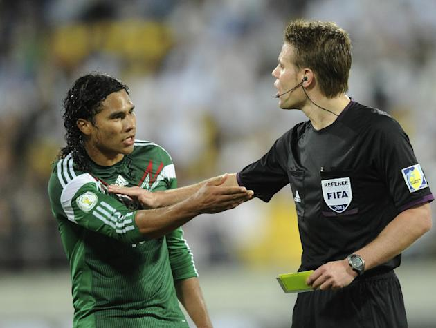Referee Felix Brych, right, holds back Mexico's Carlos Pena during the team's World Cup qualifying soccer match against New Zealand at Westpac Stadium, in Wellington, New Zealand, Wednesday, Nov. 20,
