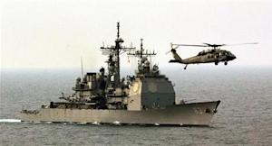 A HELICOPTER HOVERS OVER THE COWPENS GUIDED MISSILE CRUISER IN THE GULF.