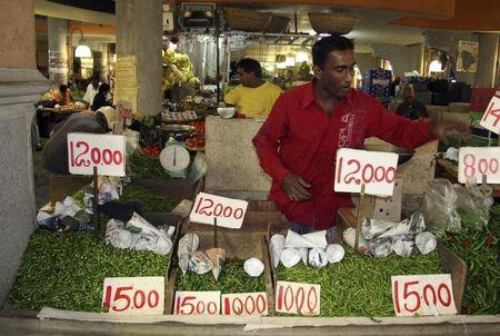 A vendor sells chillies at a food market in Port Louis