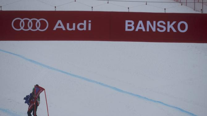 A race official removes a banner after the women's Super G event of the Alpine Skiing World Cup was cancelled due to fog in Bansko