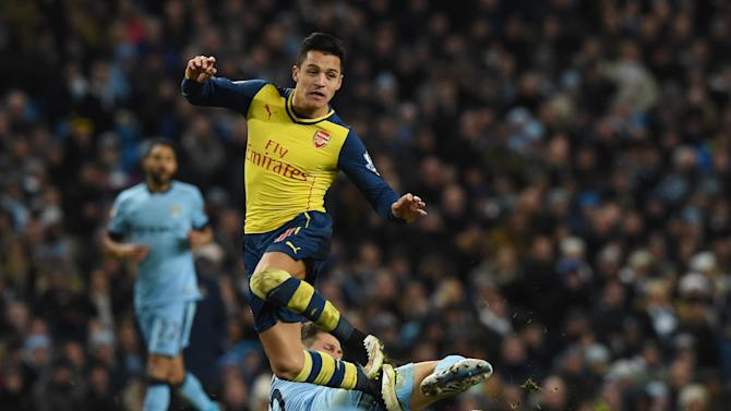 Manchester City's Martin Demichelis (ground) tackles Arsenal's Alexis Sanchez during their English Premier League match at the Etihad Stadium, on January 18, 2015