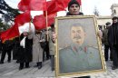 People carry red flags and a portrait of the late Soviet leader Josef Stalin during a ceremony to mark the 60th anniversary of his death in his hometown of Gori