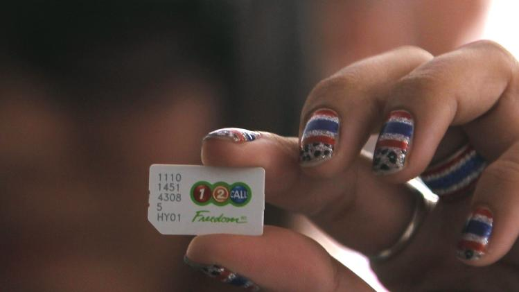An anti-government protester holds up a sim card before cancelling their AIS subscription during a rally at the Shinawatra building in central Bangkok