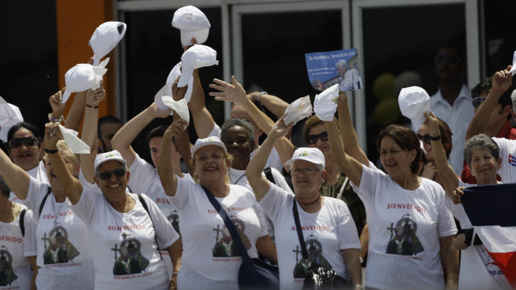 "A group of women dressed in white T-shirts with the message that reads in Spanish; ""Bienvenido,"" or ""Welcome,"" wave to the pontiff upon his arrival at the Jose Marti International airport in Havana,Cuba, Tuesday March 27, 2012. (AP Photo/Franklin Reyes)"
