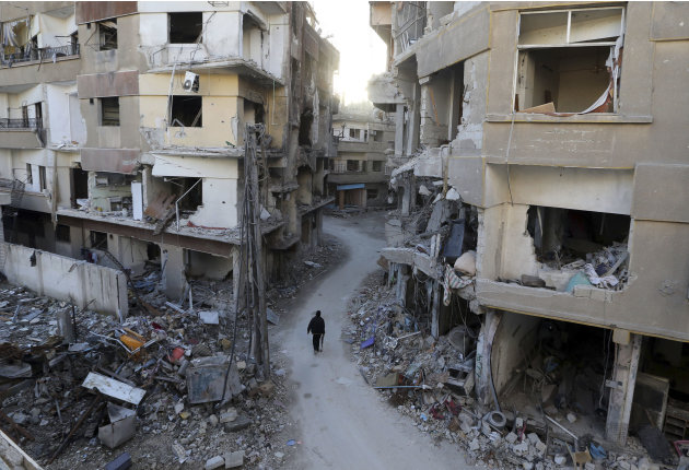 A Free Syrian Army fighter walks between buildings damaged during Syrian Air force air strikes in Haresta neighbourhood of Damascus