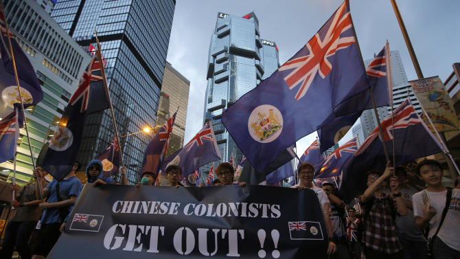Protesters raise Hong Kong colonial flags march in a downtown street during an annual pro-democracy protest in Hong Kong Monday, July 1, 2013. Tens of thousands of Hong Kong residents demanded their widely disliked Beijing-backed leader resign and pressing for promised democratic reforms so they can choose their own top representative. The march is an annual event that underscores the growing gulf between Hong Kong and the mainland 16 years after the city ceased to be a British colony and came back under Beijing's control. (AP Photo/Vincent Yu)
