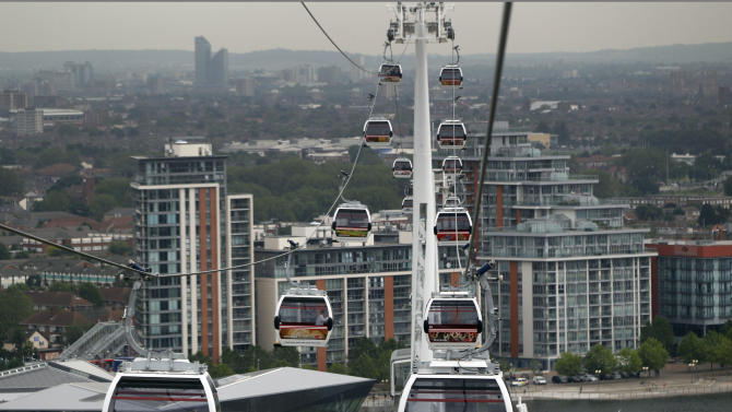 Transport for London's gondola lift cable cars are seen across the River Thames, London, Thursday, June 28, 2012. The cable car will make the half-mile (one kilometer) crossing between Greenwich and the Royal Docks, allowing visitors to take in the views of Olympic Park, the Canary Wharf financial center and the Thames Barrier. Each of the 34 cars holds 10 people and looks like the gondolas that ferry skiers up the mountains in the Swiss Alps. Travelers can go one way or round-trip, with a one-way ticket costing 3.20 pounds (5 US dollars). (AP Photo/Lefteris Pitarakis)