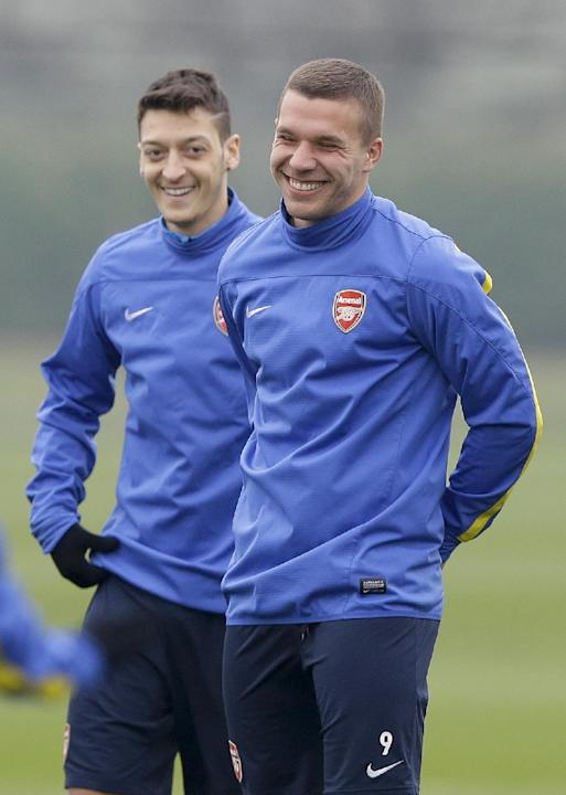Arsenal's German players Lukas Podolski, right, and Mesut Ozil smile during a training session at their London Colney training ground, Monday, March 10, 2014. Arsenal will play in a Champions Leag