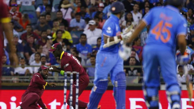 West Indies Darren Sammy catches out India's batsman Shikhar Dhawan out as West Indies Chris Gayle and India's Rohit Sharma watch on during their Cricket World Cup match in Perth