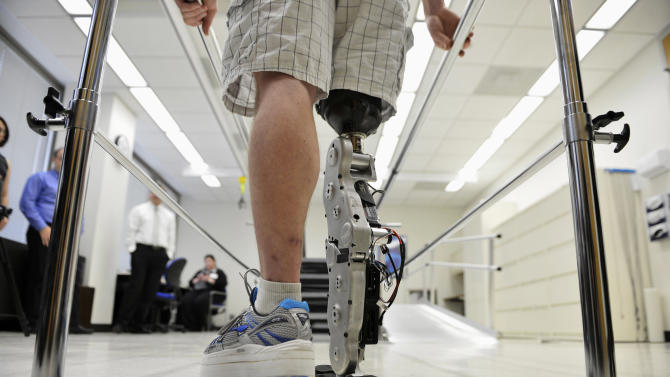"In this Oct. 25, 2012 photo, Zac Vawter practices walking with an experimental ""bionic"" leg at the Rehabilitation Institute of Chicago. After losing his right leg in a motorcycle accident, the 31-year-old software engineer signed up to become a research subject, helping test a trailblazing prosthetic leg that's controlled by his thoughts. He will put this leg to the ultimate test Sunday, Nov. 4 when he attempts to climb 103 flights of stairs to the top of Chicago's Willis Tower, one of the world's tallest skyscrapers. (AP Photo/Brian Kersey)"