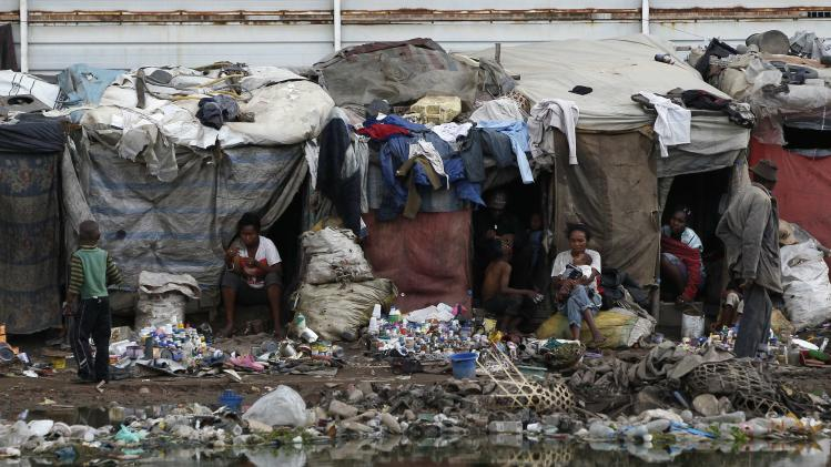 "Residents sit outside shanty houses along Andriantany waste water channel where ""La Reunion Kely"" is located in Antananarivo"