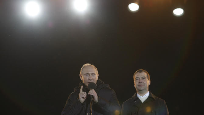 Russian Prime Minister and presidential candidate Vladimir Putin, left, gestures as he emotionally reacts at a massive rally of his supporters with Russian President Dmitry Medvedev, right, at Manezh square outside Kremlin, in Moscow, Russia, Sunday, March 4, 2012. Putin has claimed victory in Russia's presidential election, thanking his supporters for helping foil foreign plots aimed to weaken the country, an election which the opposition and independent observers say has been marred by widespread violations.  (AP Photo/Alexander Zemlianichenko Jr.)