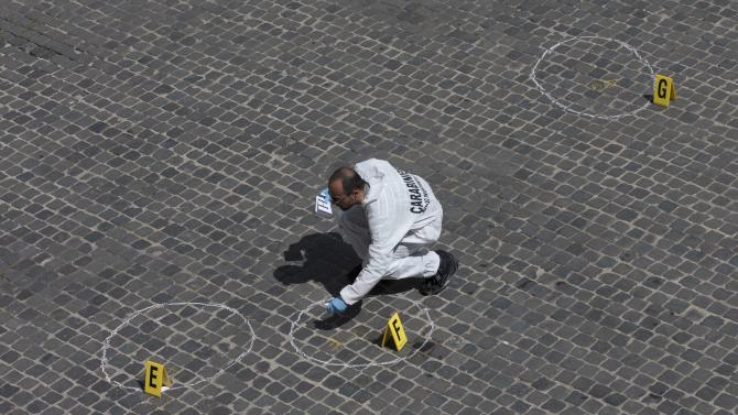 Forensic police collect evidence in Piazza Colonna Square where a shooting took place outside Chigi Palace, premier's office, building at left, in Rome, Sunday, April 28, 2013. Two Italian paramilitary policemen were shot and wounded Sunday in a crowded square outside the premier's office in Rome as Italy's new leader Enrico Letta was being sworn in at the Quirinal presidential office, about a kilometer (half-mile) away. It was not immediately clear if there was any connection between the shooting and the swearing-in. (AP Photo/Alessandra Tarantino)