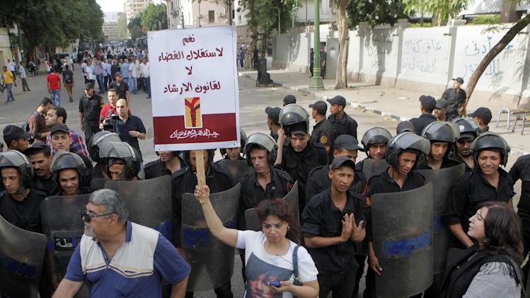 "An Egyptian opposition activist holds an Arabic poster which reads, ""Yes for judicial independence, no for Brotherhood law,"" as  anti-riot soldiers prevent activists from reaching the Shura Council, the upper house of Parliament, during a protest against the new judicial law in Cairo, Egypt, Saturday, May 25, 2013.  (AP Photo/ Amr Nabil)"