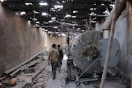 Free Syrian Army fighters walk with their weapons in a damaged factory in the al-Khalidiya neighbourhood of Aleppo, September 21, 2013. REUTERS/Aref Hretani