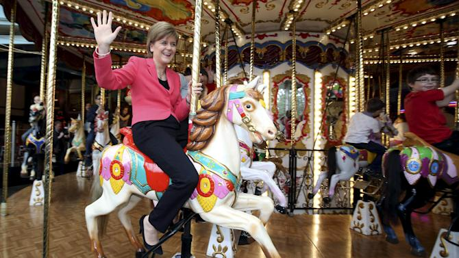 First Minister for Scotland Nicola Sturgeon poses for a photograph on a carousel during a campaign visit to a theme park in Motherwell, central Scotland