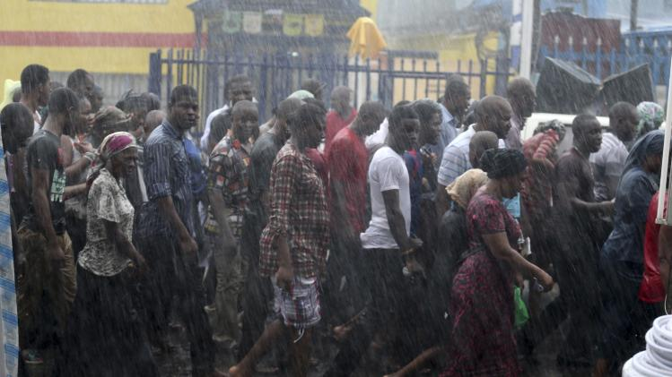 Catholic faithful walk in the rain during a procession re-enacting the death of Jesus Christ, on Good Friday in Lagos
