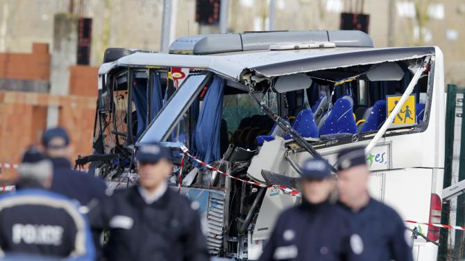 French police work at the scene near the wreckage of a school minibus after it crashed into a metal panel which fell from a truck in Rochefort