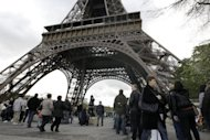Visitors line up in front of the Eiffel Tower in Paris after an elevator broke down