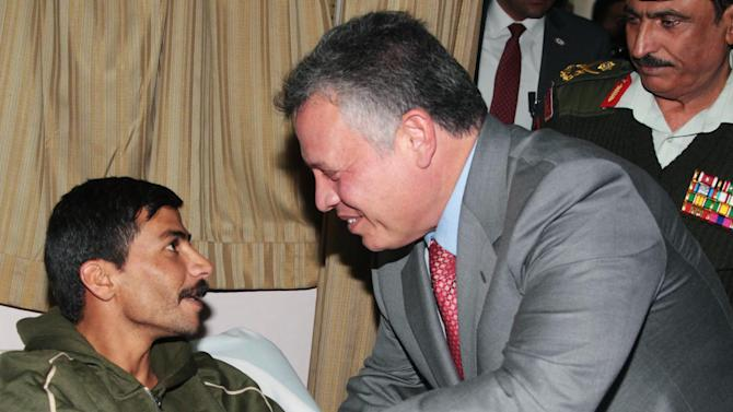 In this photo released by the Jordanian Royal Palace, Jordan's King Abdullah II, right, shakes hands with a policeman wounded in unrest that swept the kingdom this week, killing one person and wounding tens of others, including policemen at a hospital in Amman, Jordan, Sunday, Nov. 18, 2012. Protests across the country featuring rare calls for the overthrow of the king turned unusually violent last week.(AP Photo/Yousef Allan, Jordanian Royal Palace)