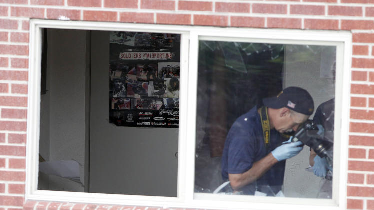 "FBI agents photograph the bedroom in the apartment of alleged gunman James Holmes with a poster titled ""Soldiers of Misfortune"" Saturday, July 21, 2012 in Aurora, Colo. Authorities reported that 12 died and more than three dozen people were shot during an assault at a movie theatre midnight premiere of ""The Dark Knight Rises."" (AP Photo/Alex Brandon)"