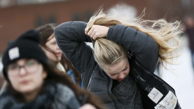 A women holds her hair together as she crosses the Millennium Bridge during strong winds in London
