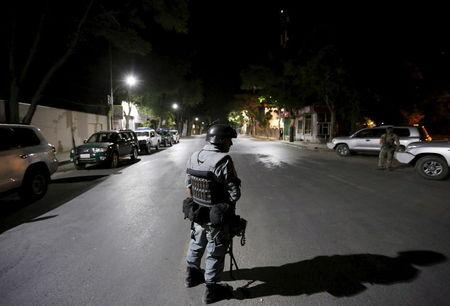 Afghan policeman keeps watch near the site of an attack in Kabul,Afghanistan