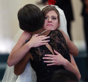Aurora shooting survivor, and now newlywed, Kirstin Han hugs her new mother-in-law Rosa Han, shortly after Kirstin and her husband Eugene Han exchanged vows, during their wedding ceremony at Village East Baptist Church, in Aurora, Colo. Saturday July 20, 2013. One year to the day since Eugene was shot while trying to protect his longtime girlfriend Kirstin - then Kirstin Davis - from harm during a shooting rampage in an Aurora theater, the two have become man and wife. (AP Photo/Brennan Linsley)
