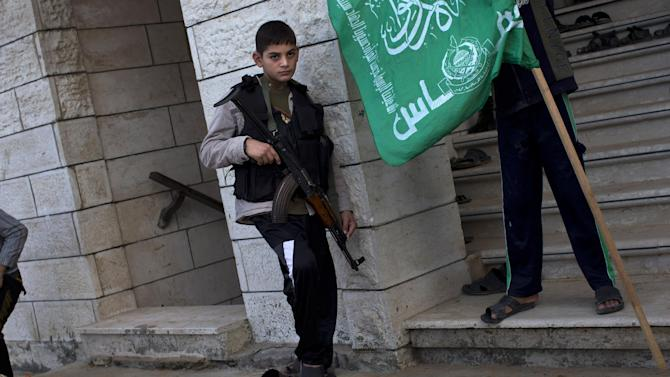 A Palestinian child holds a Kalashnikov weapon from a Hamas member, not pictured, during the funeral of Hamas member Joudeh Shamallah in Gaza City, Saturday, Nov. 24, 2012. According to family members, Shamallah was badly injured during the latest Israeli-Hamas fight and died from wounds Saturday. (AP Photo/Bernat Armangue)