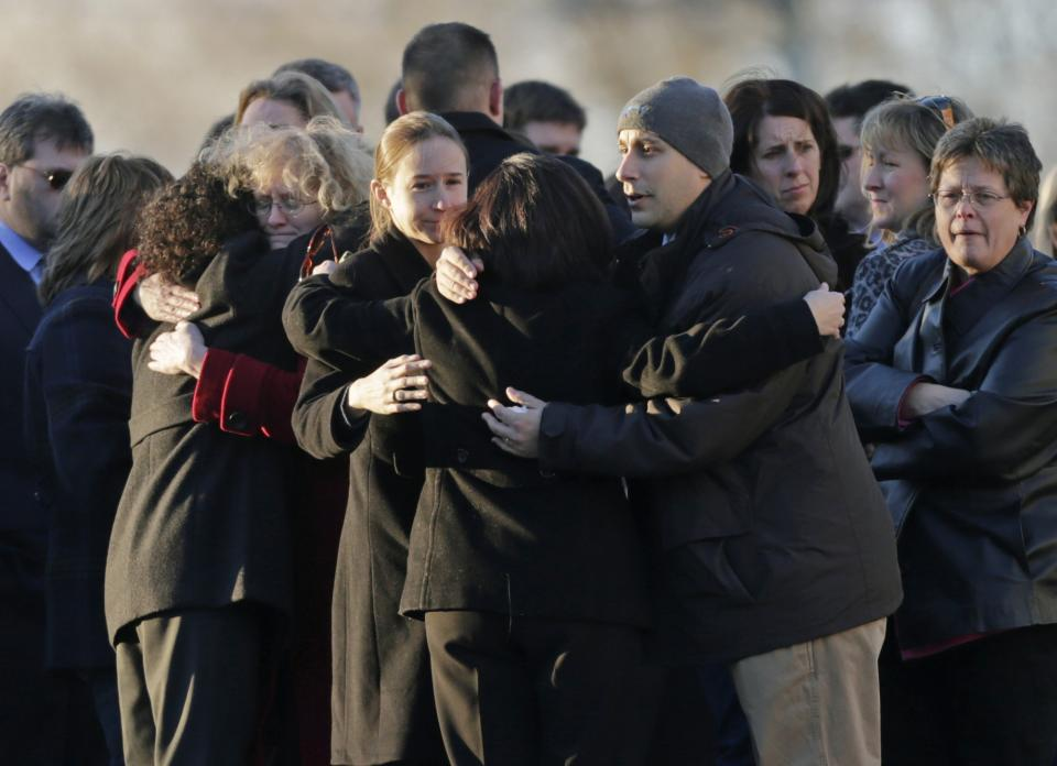 DAWN HOCHSPRUNG, 47, principal: Mourners embrace at Hochsprung's wake in Woodbury, Conn., Wednesday, Dec. 19, 2012. (AP Photo/Charles Krupa)