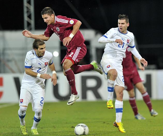 Latvia's Vitalijs Maksimenko, centre, vies for the ball with Slovakia's Peter Pekarik, left, and Michal Duris during their World Cup 2014 Group G qualification match in Riga, Latvia, on Tuesday. Octob