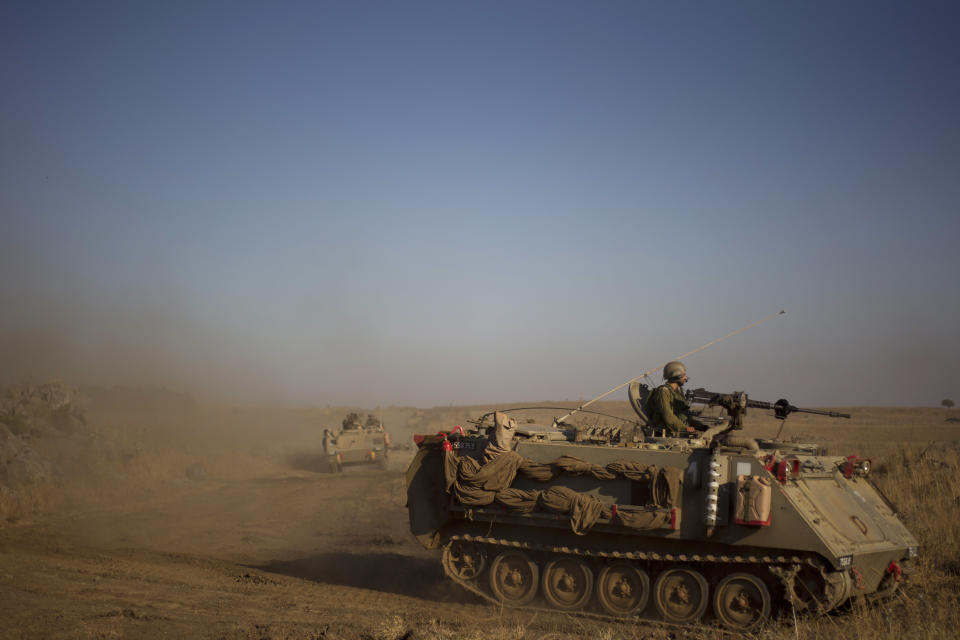 Israeli soldiers from the Golani brigade drive their APC (Armored Personnel Carrier) during a military exercise in the Israeli-controlled Golan Heights near the border with Syria Tuesday, June 25, 2013. (AP Photo/Ariel Schalit)