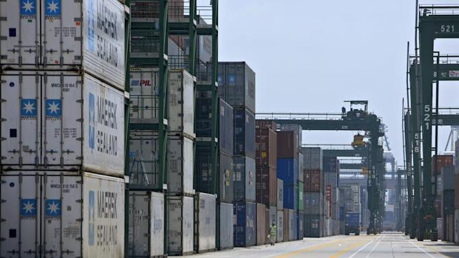 A worker walks past stacks of containers at the PSA International's Pasir Panjang terminal in Singapore