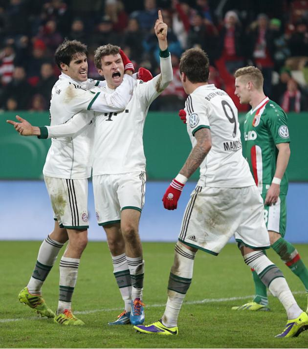 Bayern's Thomas Mueller, center, celebrates with teammates Mario Mandzukic of Croatia, right, and Javier Martinez of Spain after scoring his side's second goal during the German soccer cup thi
