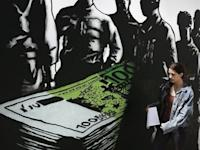 """A woman makes her way past graffiti """"Death of euros"""" made by French street artist Goin in Athens"""