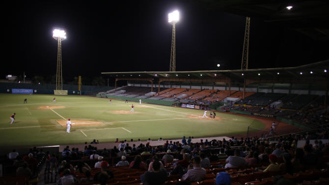 In this Dec. 29, 2012 photo, fans watch a baseball game in Caguas, Puerto Rico. It's been years since the golden era of Puerto Rican baseball, when players like Orlando Cepeda, Roberto Alomar, Ivan Rodriguez, Carlos Delgado and Carlos Beltran made their debuts. But there are signs of a baseball revival in Puerto Rico. (AP Photo/Ricardo Arduengo)