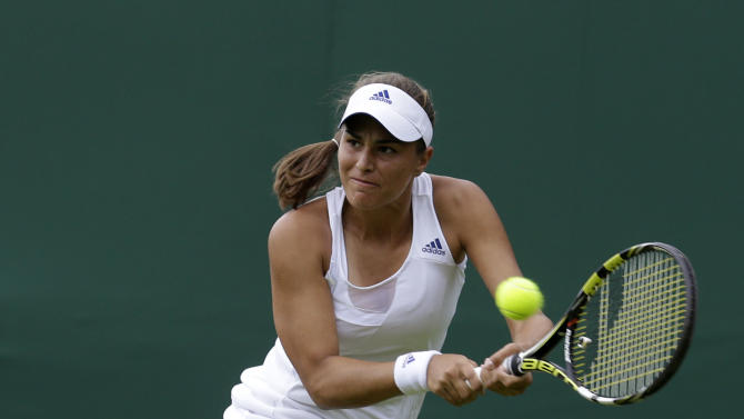 Monica Puig of Puerto Rico returns the ball to Sara Errani of Italy during their Women's first round singles match at the All England Lawn Tennis Championships in Wimbledon, London, Monday, June 24, 2013. (AP Photo/Anja Niedringhaus)