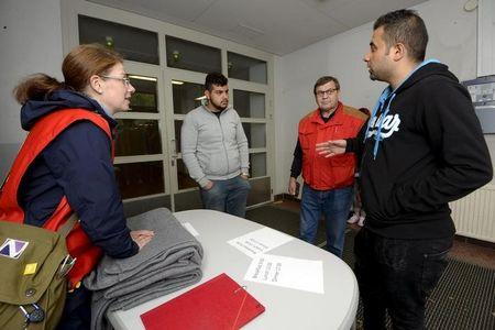 Iraqi asylum seekers speak to Finnish Red Cross workers in a refugee center in Lahti