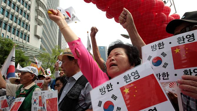 "Conservative activists shout during a rally welcoming Chinese President Xi Jinping's visit to South Korea, near the Chinese Embassy in Seoul, South Korea, Wednesday, July 2, 2014. Xi's first visit to the Korean Peninsula as China's president is to Seoul, not Pyongyang, meaning that North Korea's best friend has snubbed it for its most bitter rival. A flurry of recent rocket and missile tests, the latest on Wednesday, has made the North's displeasure crystal clear. The writing on the cards reads "" Welcome. Visit to South Korea."" (AP Photo/Ahn Young-joon)"