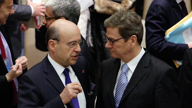 French Foreign Minister Alain Juppe, left, and German Foreign Minister Guido Westerwelle meet before the Security Council meeting at United Nations headquarters, Monday, March 12, 2012. The bloody conflict in Syria is likely to dominate public and private talks Monday as key ministers meet at the United Nations on the Israeli-Palestinian conflict and challenges from the Arab Spring. (AP Photo/Richard Drew)