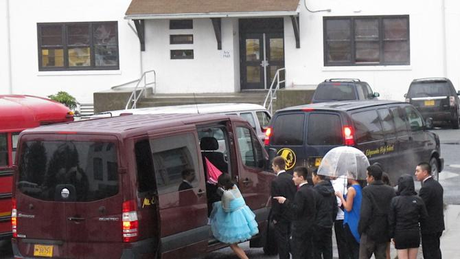 In this photo taken March 30, 2013, in Sitka, Alaska, Mount Edgecumbe High School students shield their formal wear from the rain as they load vans for their off-campus dinners ahead of the annual prom. Mount Edgecumbe is Alaska's only boarding school, and many of the 360 students who attended prom come from more than a hundred Alaska villages. The Prom Princess program began five years ago by Alaska Airlines employees and retirees. It secures donated dresses and brings in hair stylists and nail artists to get the students ready for their prom. (AP Photo/Mark Thiessen)