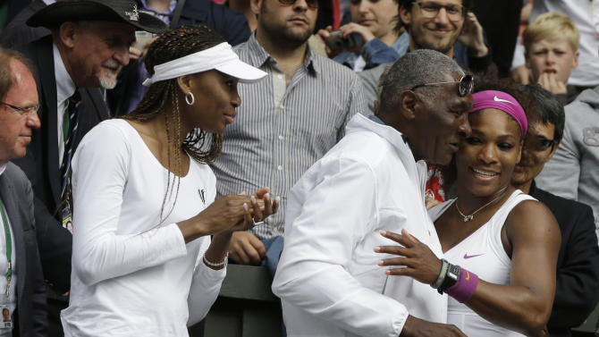 Serena Williams of the United States, right, embraces her father Richard Williams, center, as her sister Venus looks on, after she defeated Agnieszka Radwanska of Poland to win the women's final match at the All England Lawn Tennis Championships at Wimbledon, England, Saturday, July 7, 2012. (AP Photo/Kirsty Wigglesworth)